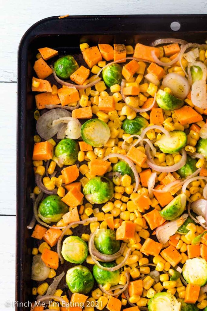 Sheet pan of cut Brussels sprouts, diced sweet potatoes, shallots, and corn