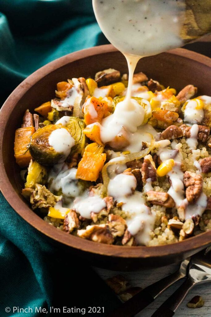 Creamy mozzarella sauce being drizzled over a roasted vegetable quinoa harvest bowl with Brussels sprouts, quinoa, corn, sweet potatoes, shallots, and pecans
