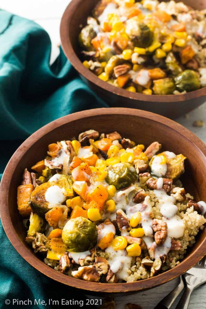 Two roasted vegetable quinoa harvest bowls in wooden bowls with Brussels sprouts, quinoa, corn, sweet potatoes, shallots, pecans, and a creamy mozzarella sauce