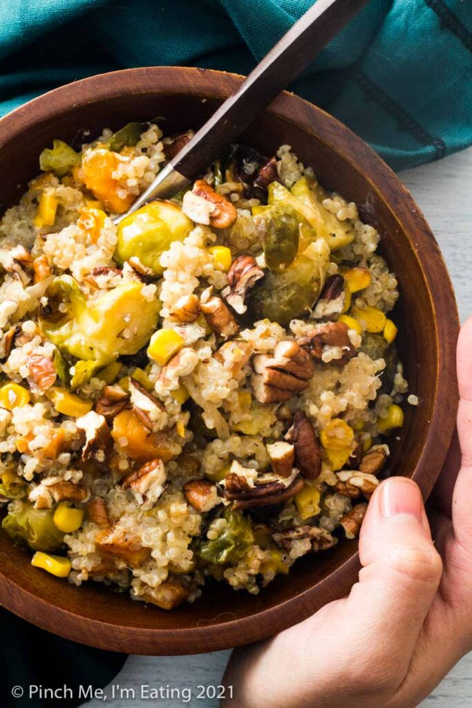 A hand holding a wooden bowl of Brussels sprouts, sweet potatoes, corn, shallots, quinoa, and pecans