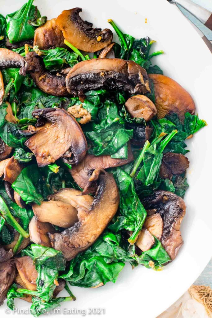 Close up overhead view of sautéed spinach and mushrooms in a white bowl