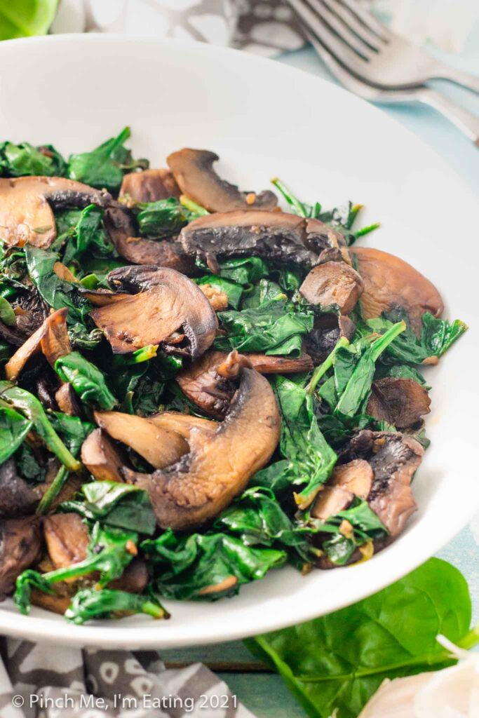 Three quarter view of sautéed spinach and browned mushrooms in a white bowl