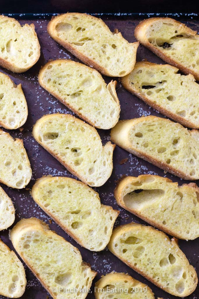 Overhead view of crostini on a baking sheet
