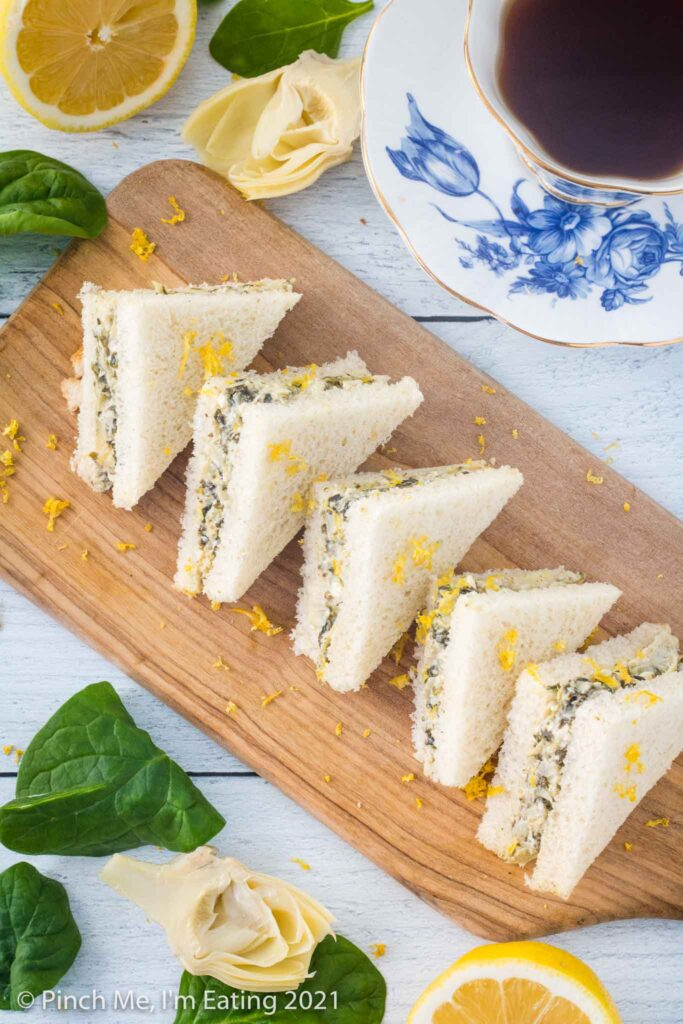 Overhead shot of artichoke spinach tea sandwiches arranged on a diagonal cutting board and topped with lemon zest. A blue and white teacup, half a lemon, artichoke, and spinach leaves are beside the board.