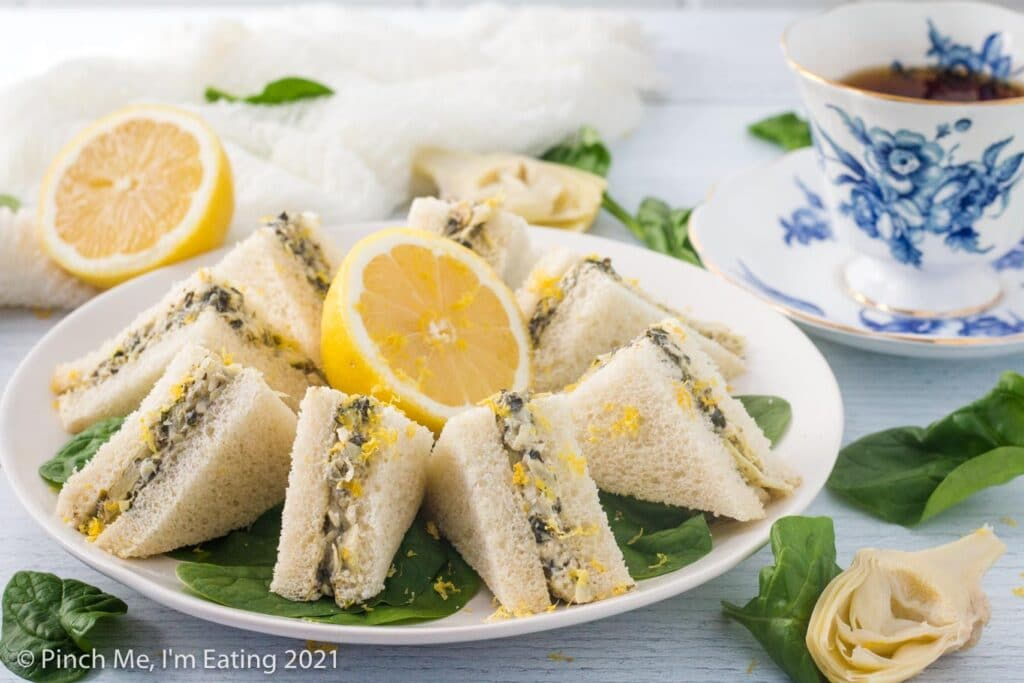 Three quarter view of artichoke spinach tea sandwiches arranged on a diagonal cutting board and topped with lemon zest. A blue and white teacup, half a lemon, artichoke, and spinach leaves are beside the board.