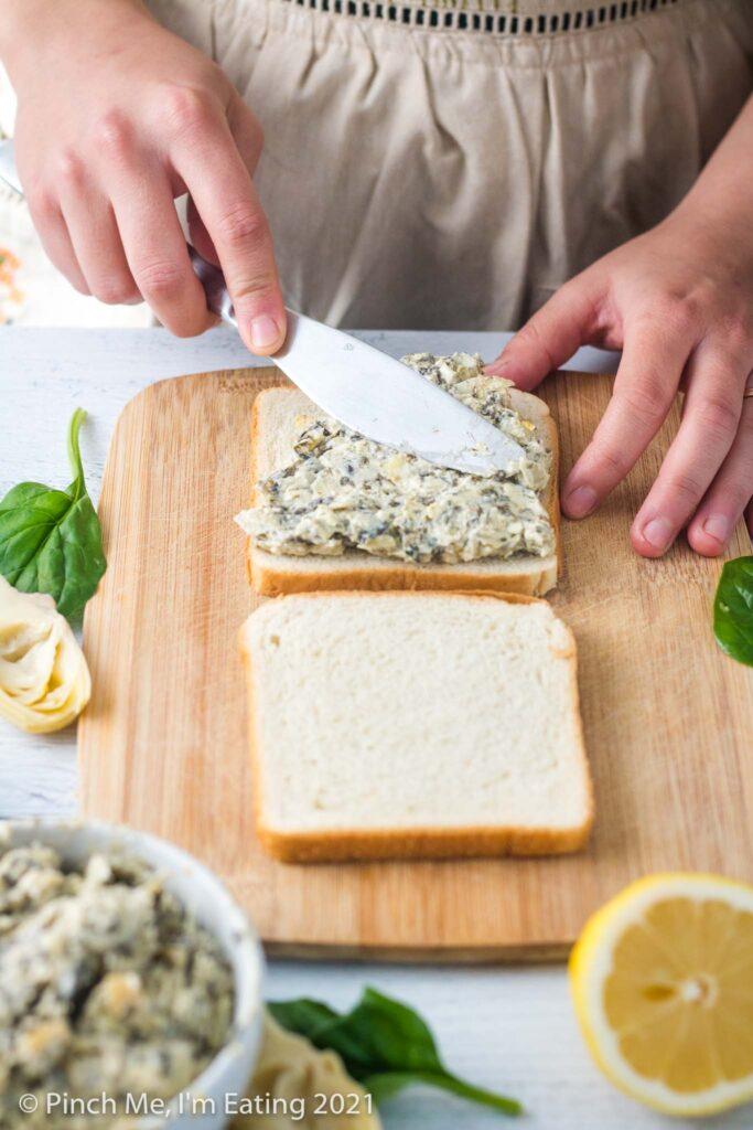 Spreading artichoke spinach dip on slice of white bread