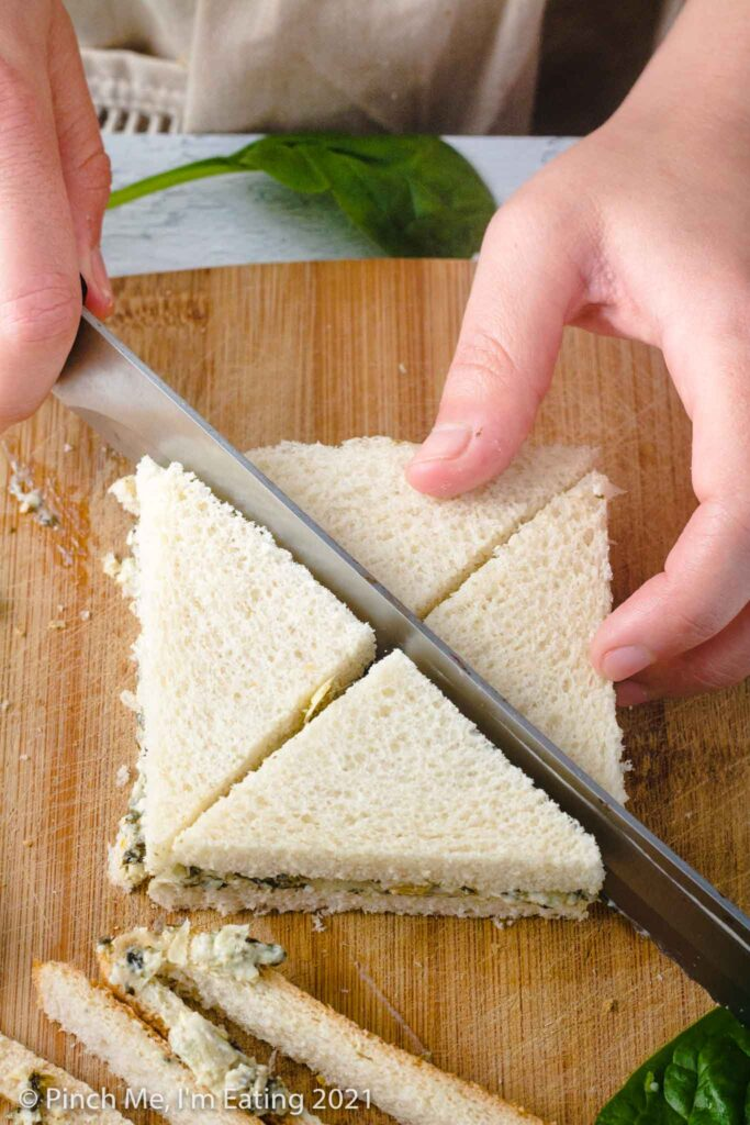 Cutting crustless sandwich into four triangles with serrated bread knife