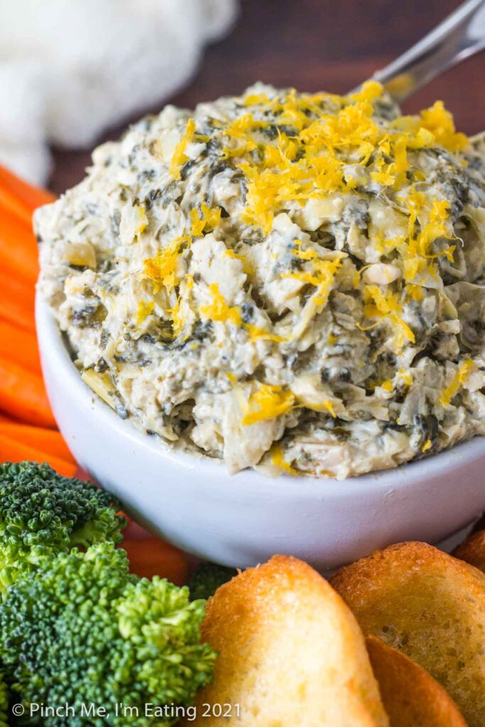 Three quarter view of white bowl of cold artichoke spinach dip topped with lemon zest, surrounded by crostini and fresh vegetables