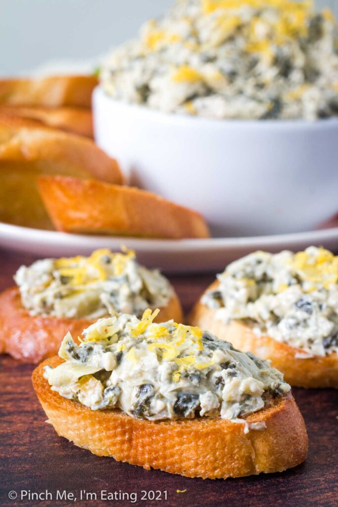 Crostini topped with cold artichoke spinach dip with lemon zest