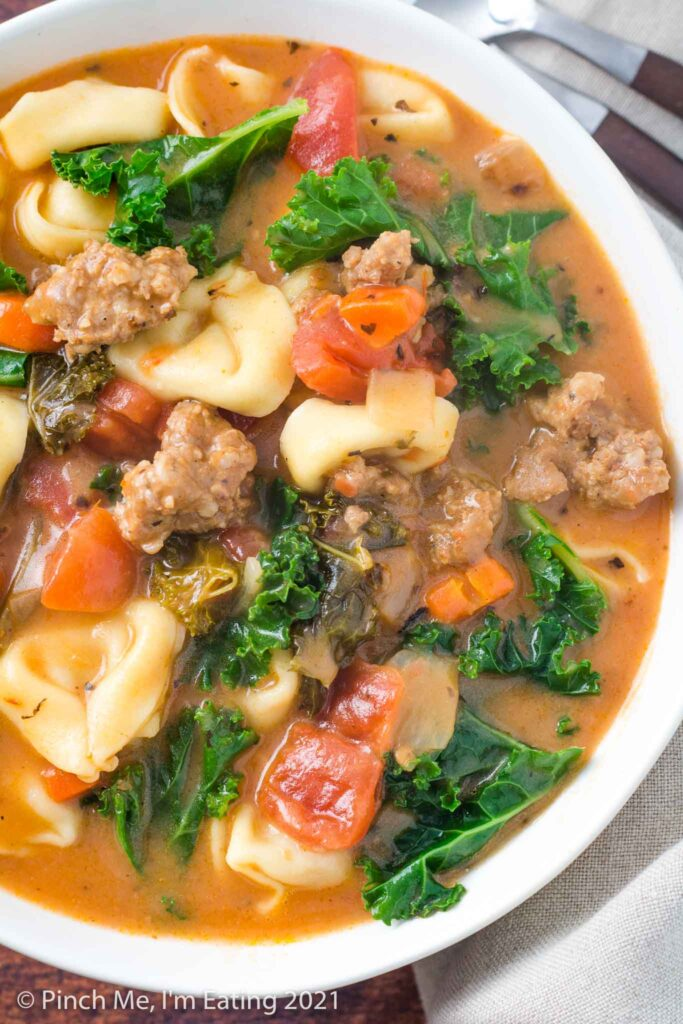 Overhead view of a closeup of a white bowl of Italian sausage soup with tortellini and kale