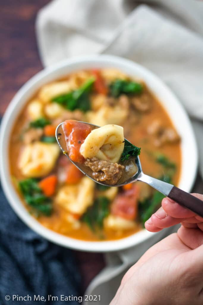 Overhead view of a spoonful of Italian sausage soup with tortellini and kale over a white bowl of soup