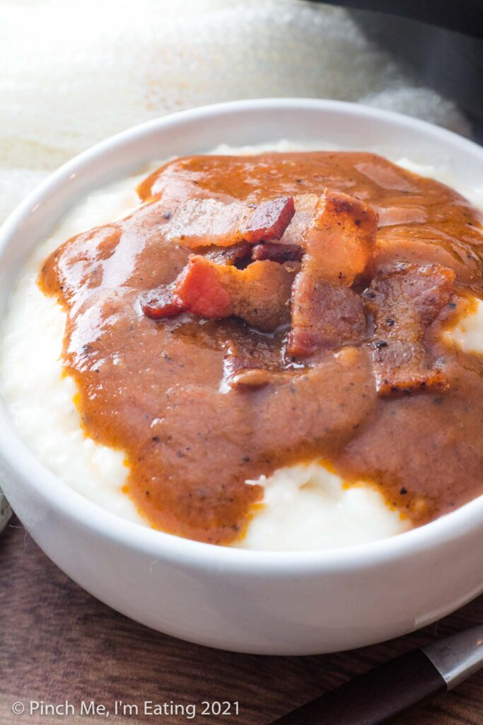 Close up view of grits in white bowl topped with bacon and Southern tomato gravy