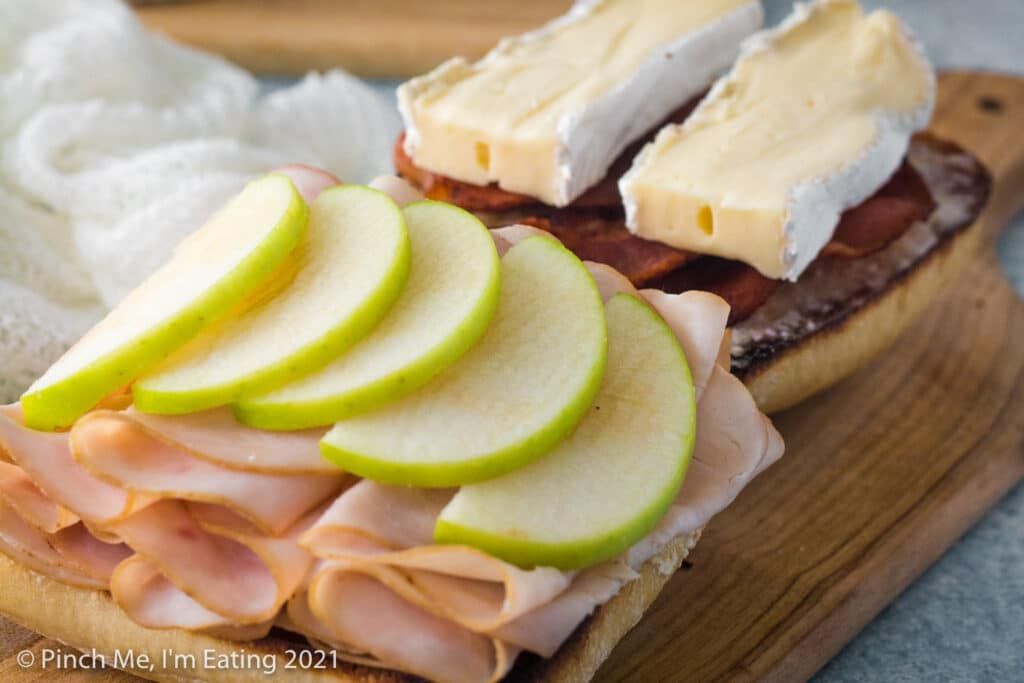 Bottom of ciabatta roll is layered with smoked deli turkey and green Granny Smith apple while top of roll is layered with bacon and brie cheese