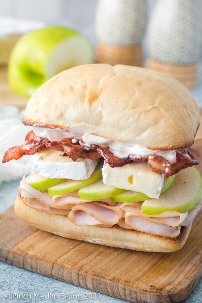 A sandwich sitting on a wooden cutting board is layered on a ciabatta roll with smoked deli turkey, green granny smith apple, brie cheese, bacon, and garlic mayo.