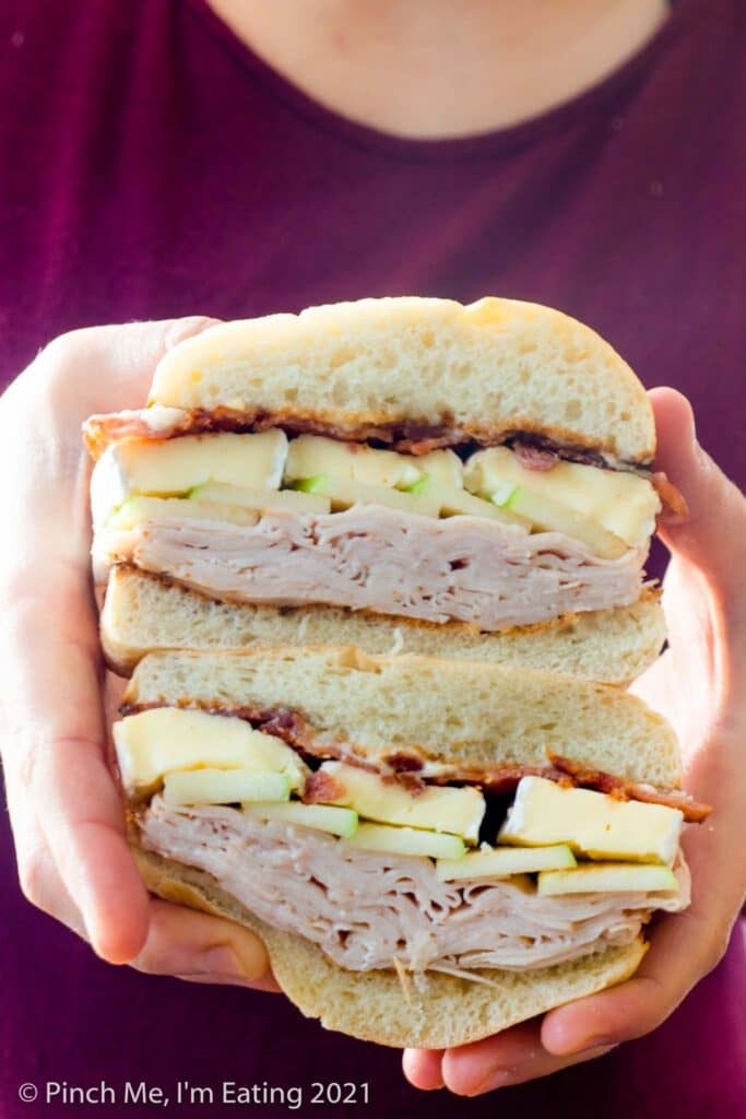 White woman holding a smoked turkey, bacon, and brie sandwich cut in half