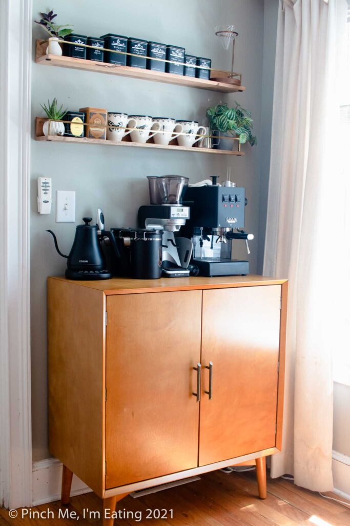 Modern DIY kitchen coffee bar station cabinet with floating shelves, mugs, tea tins, espresso machine, and electric kettle