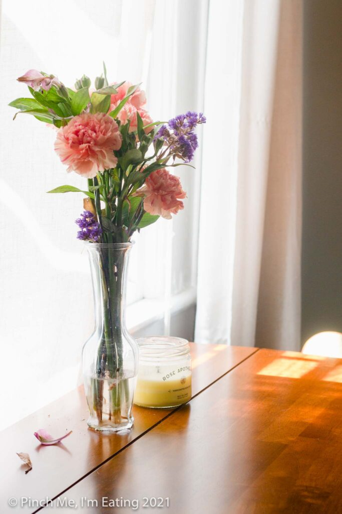 Cafe table in dining room next to airy window with candle and fresh flowers