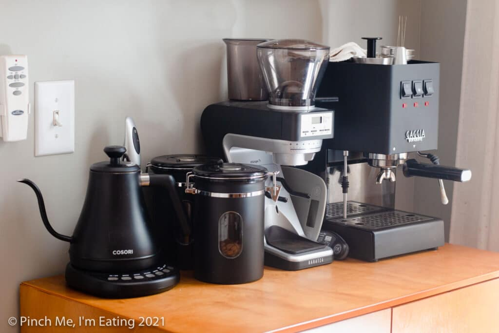 Modern DIY at-home kitchen coffee bar station cabinet with espresso machine, coffee canisters, and electric kettle