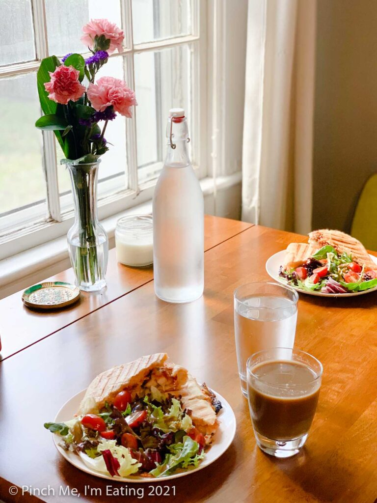 Cafe table in dining room next to window with fresh flowers and paninis on white plates with side salads. Water is in a glass water bottle.