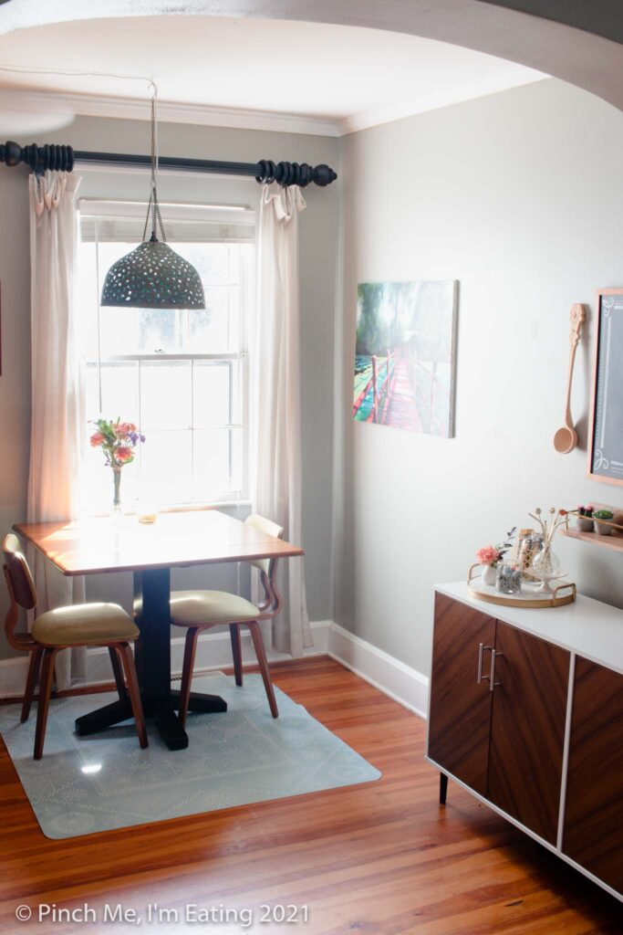 Cafe table in dining room next to window with pendant light and fresh flowers and DIY home coffee bar station on a buffet table