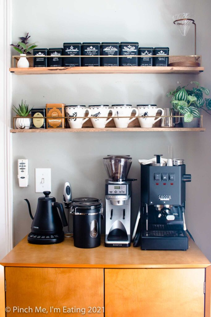 Modern DIY kitchen coffee bar station cabinet with floating shelves, mugs, tea tins, pourover stand, faux succulents, espresso machine, coffee canisters, and electric kettle