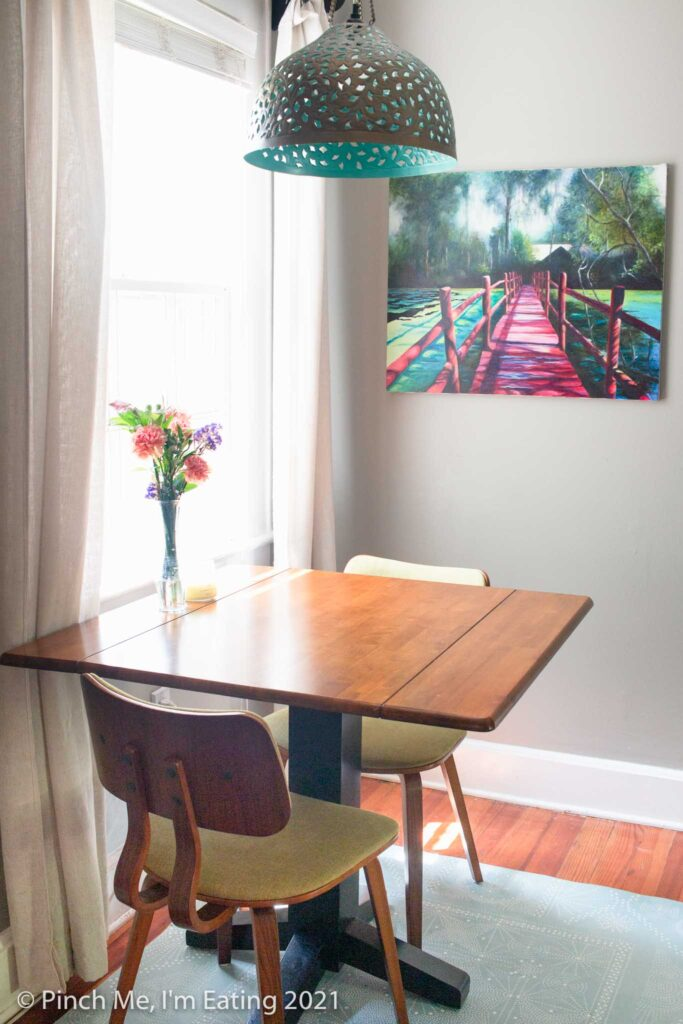 Cafe table in dining room next to window with pendant light and fresh flowers with art on the wall