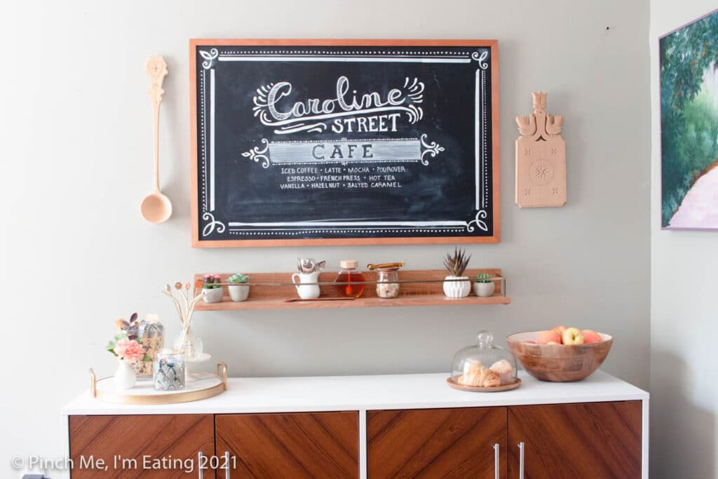 DIY at-home coffee station ideas - coffee bar on dining room buffet with fruit bowl and pastry display, floating shelf, and menu chalkboard