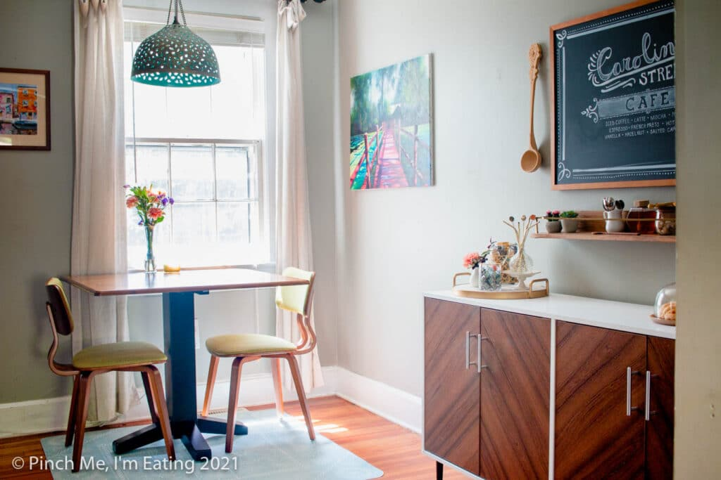 Cafe table in dining room next to window with pendant light and fresh flowers and DIY home coffee bar station on a buffet table with floating shelf and menu chalkboard