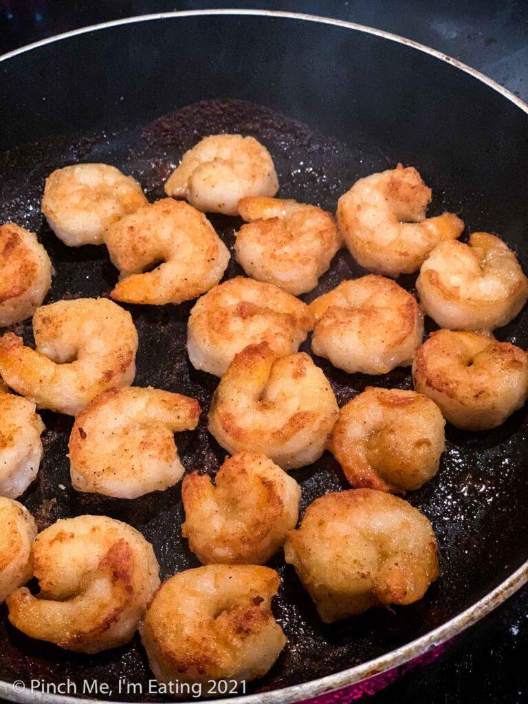 Lightly breaded shrimp frying in a skillet