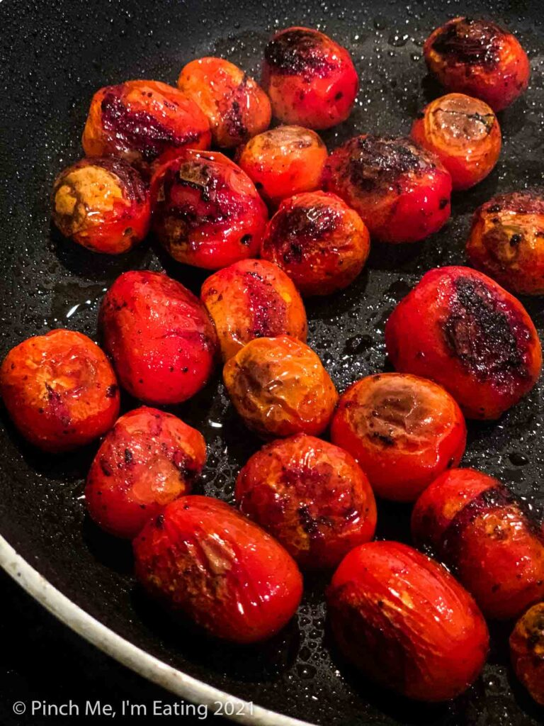 Blistered charred grape tomatoes in a black skillet