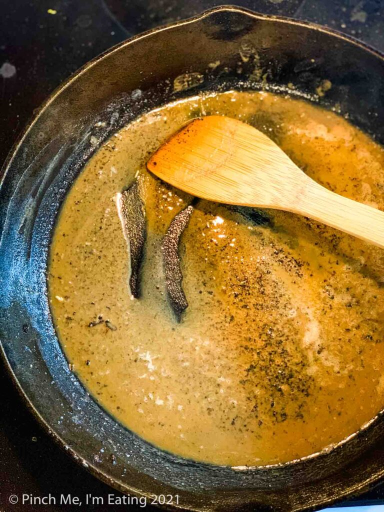 A golden roux of bacon grease and flour in a cast iron skillet with a wooden spoon