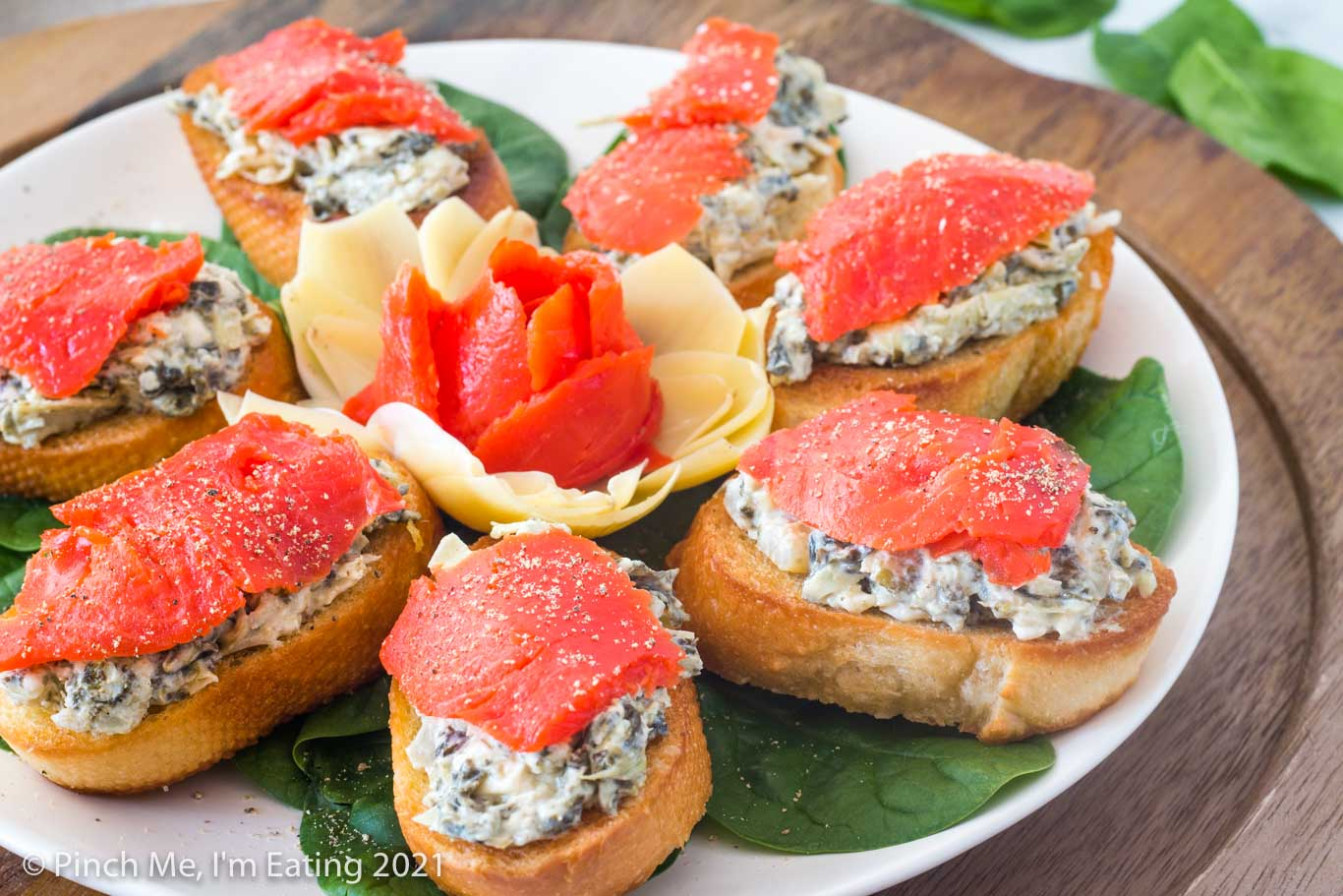 Artichoke spinach dip crostini with smoked salmon arranged in on a white plate around a flower made of artichoke heart and smoked salmon