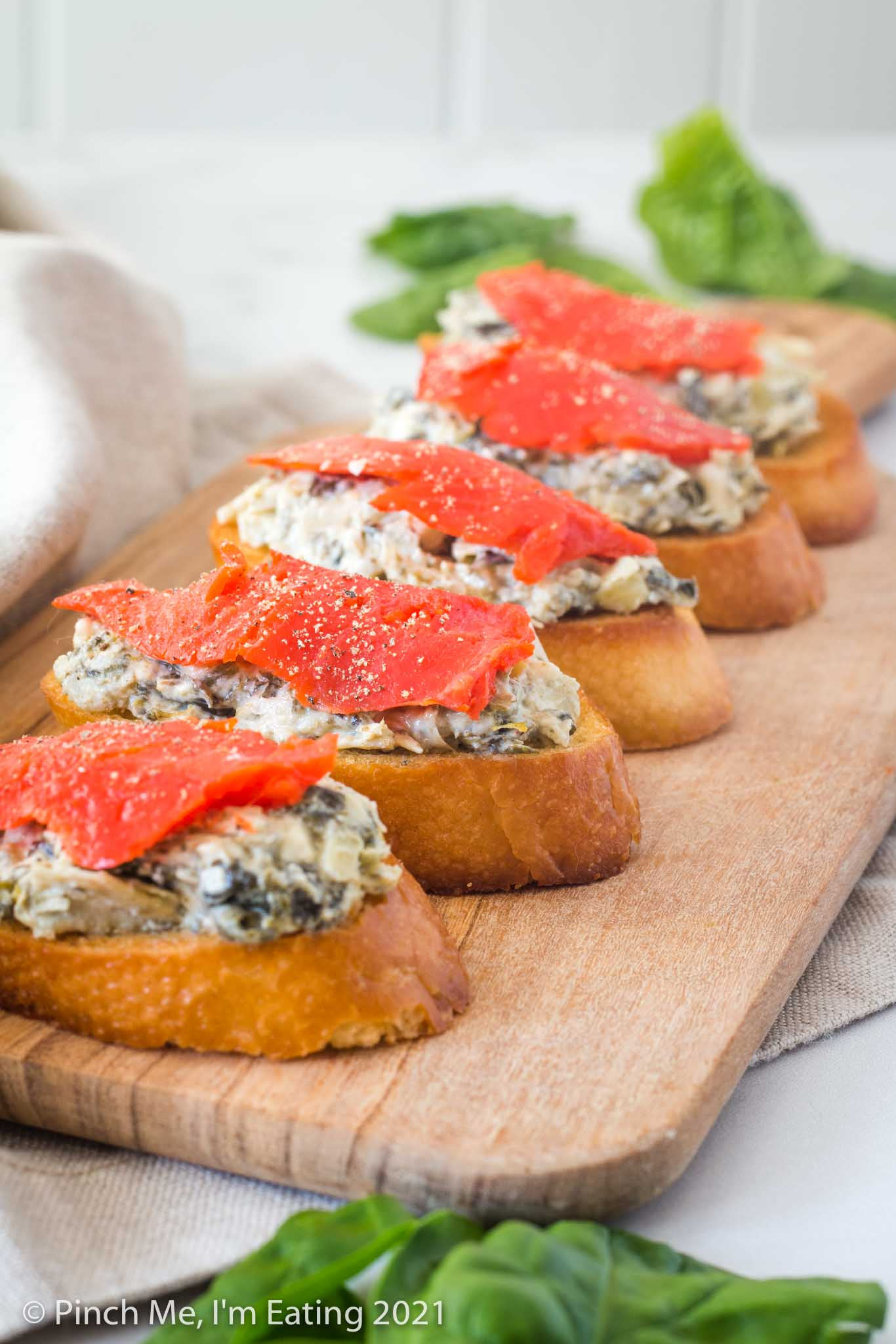 Spinach artichoke crostini with smoked salmon on a wooden cutting board