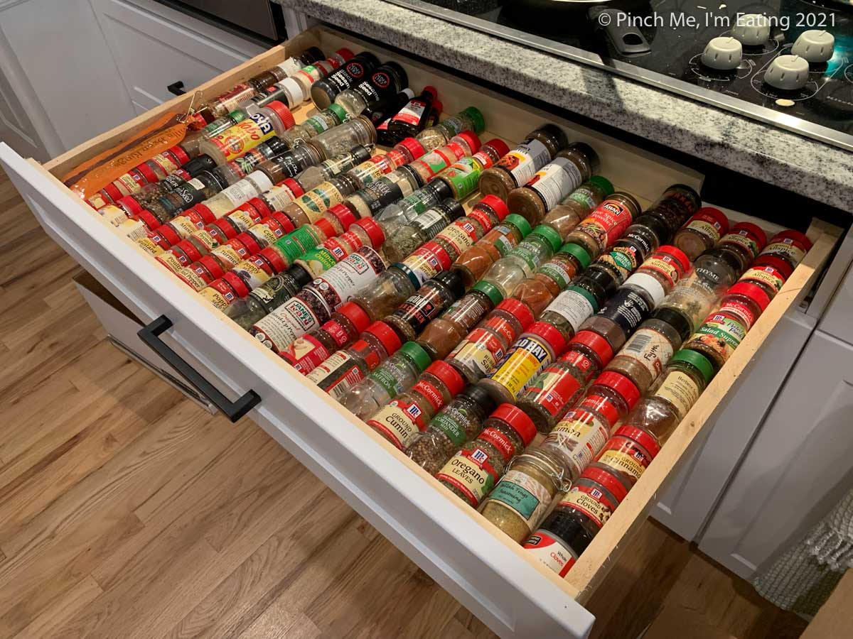 Cluttered, disorganized spices lined up in a drawer in their original containers