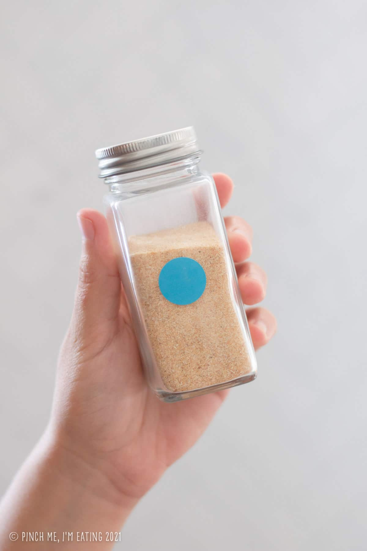 Hand holding glass jar of garlic powder with round blue sticker to denote backstock is available